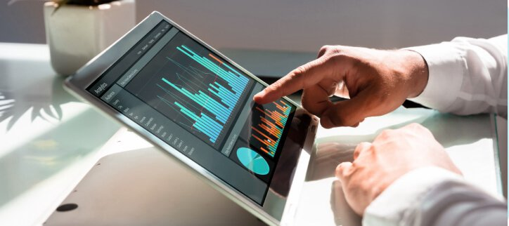 Image of man tapping data graph on laptop touchscreen