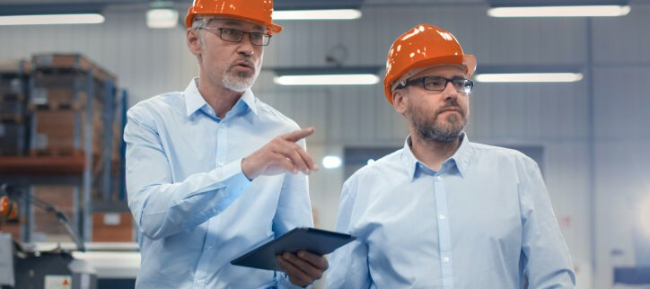 Image of men walking through factory with tablet